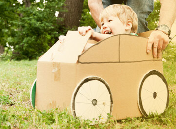 Child in cardboard car